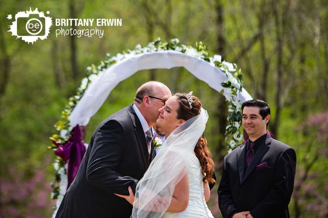 Father-of-the-bride-handing-off-with-cheek-kiss-outdoor-ceremony-groom-reaction.jpg