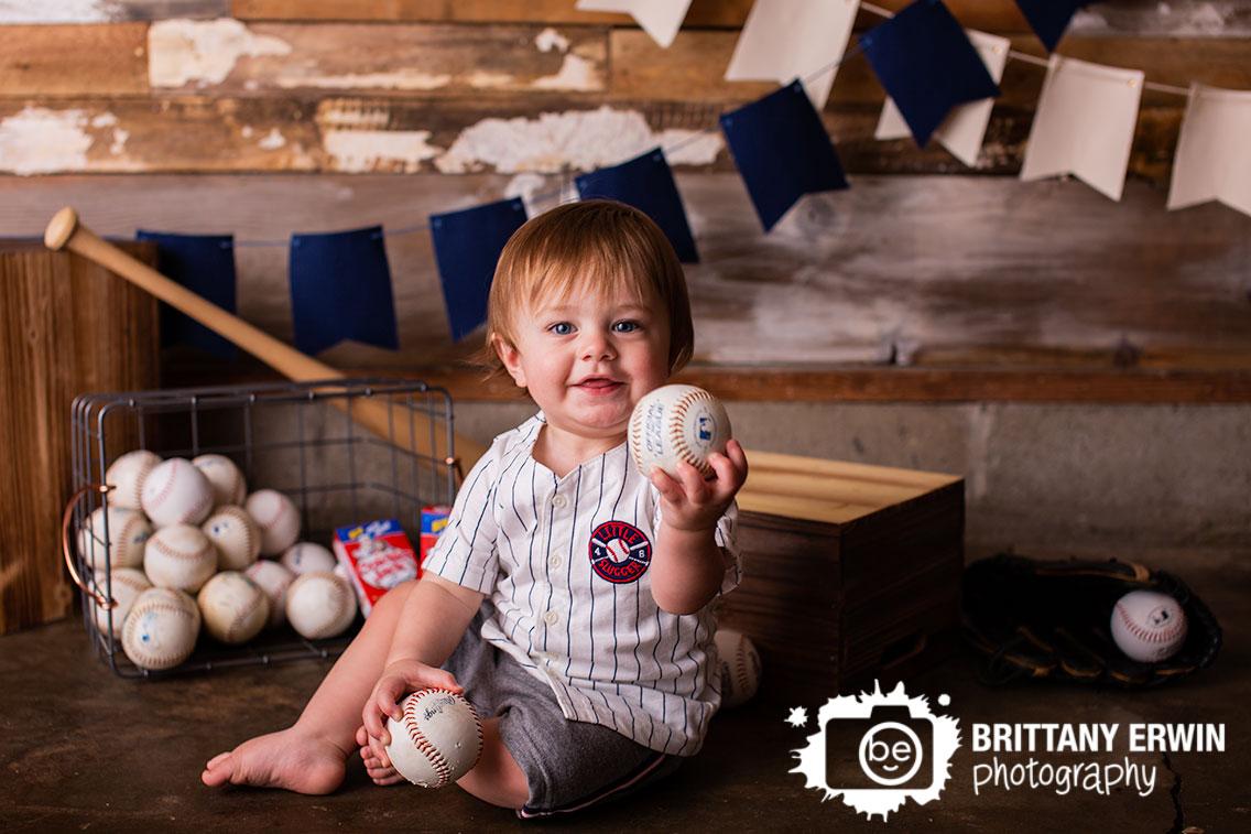 Baby-boy-holding-baseballs-little-slugger-outfit-birthday-studio.jpg