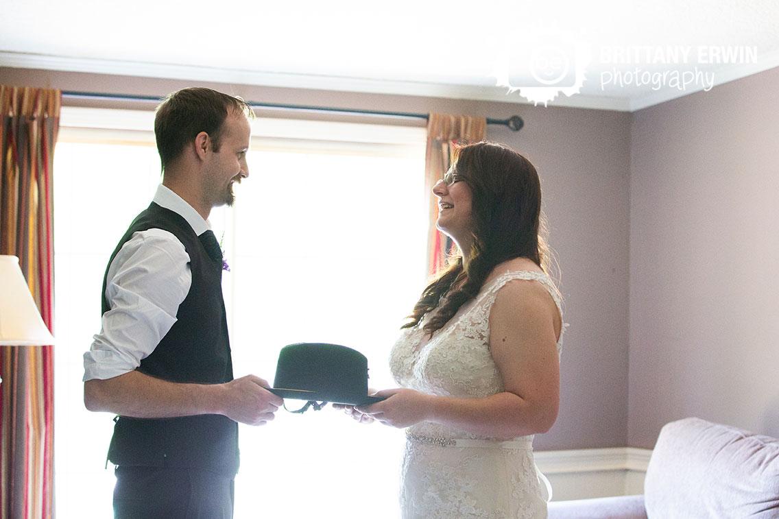 Bride-groom-hand-off-calvary-hat-before-ceremony.jpg