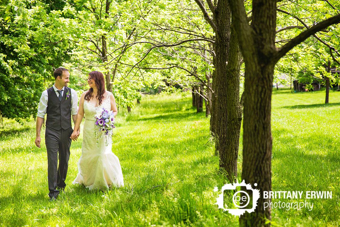Indiana-elopement-photographer-bride-groom-walk-by-walnut-tree-line-purple-bouquet.jpg