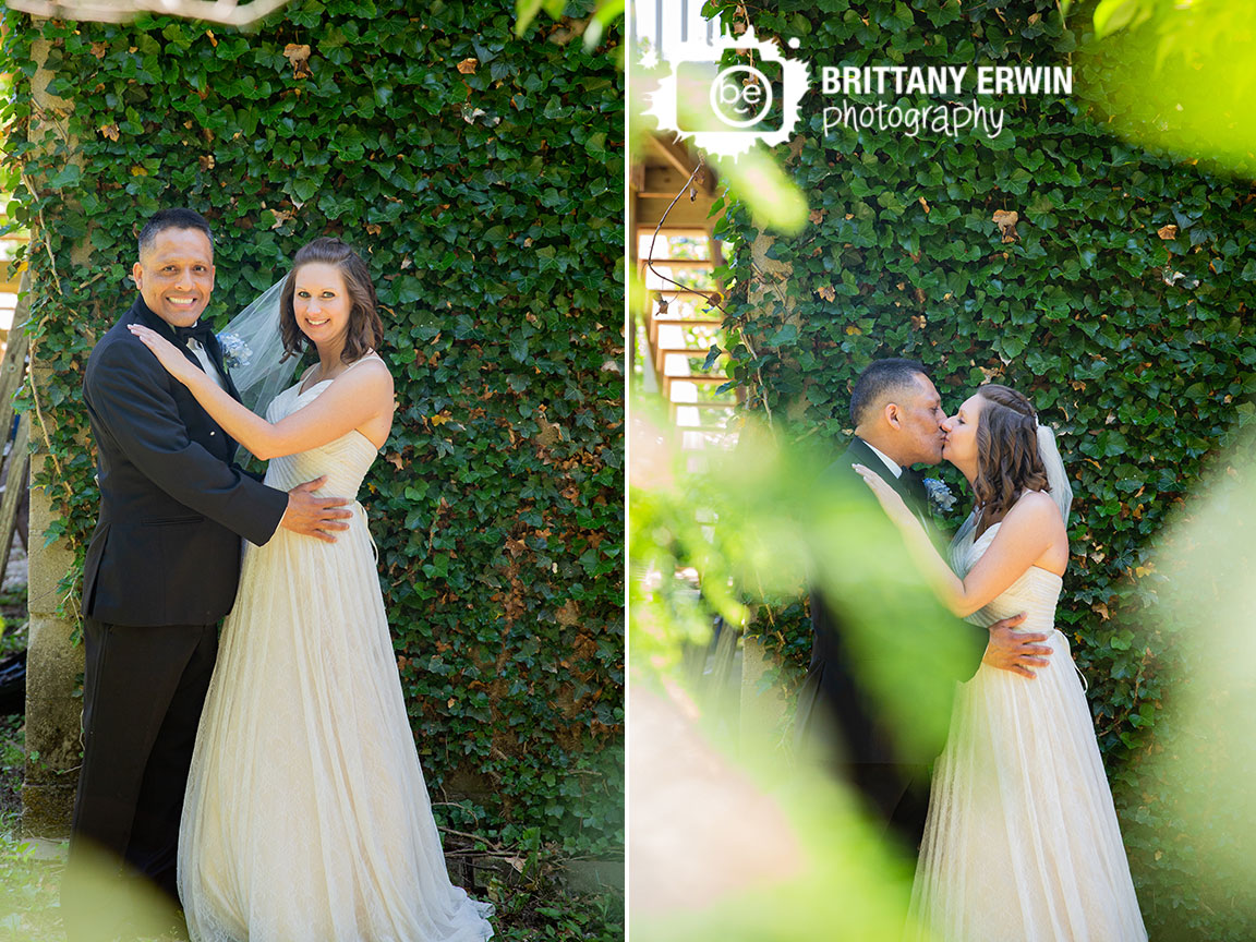 Ivy-covered-wall-bride-groom-kiss-outdoor-wedding-photographer.jpg