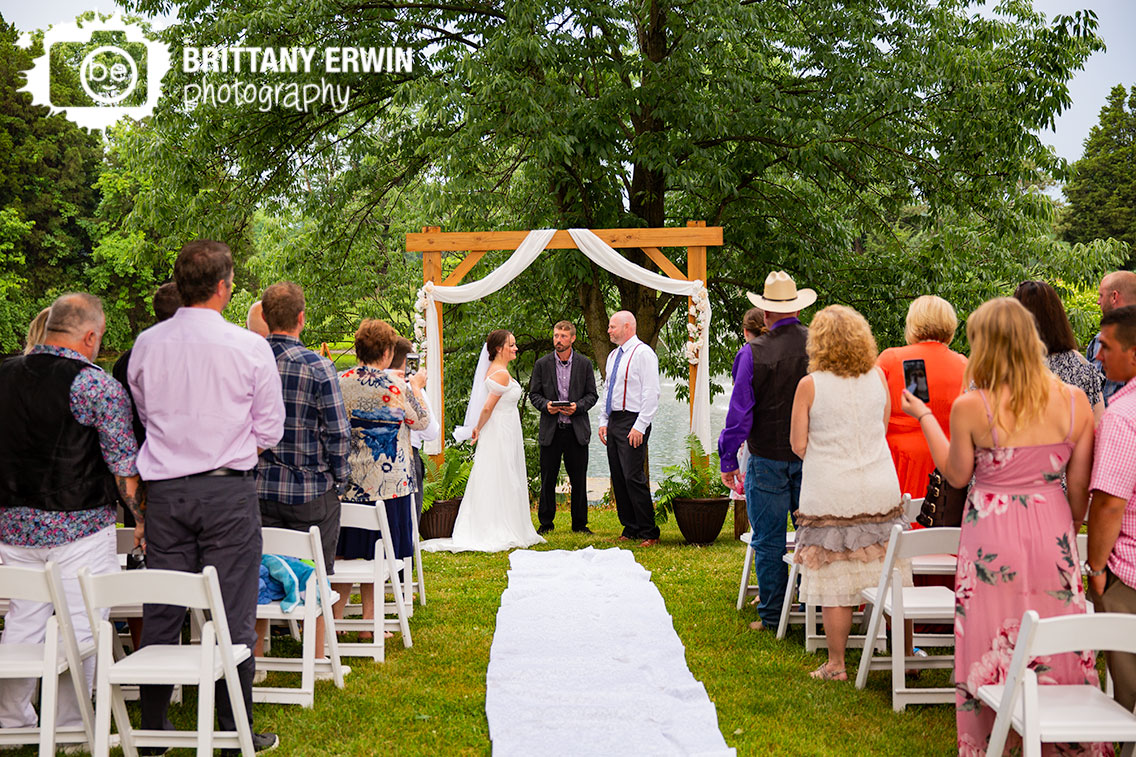 Wedding-ceremony-photographer-couple-at-altar-wooden-arbor-with-white-drapery.jpg