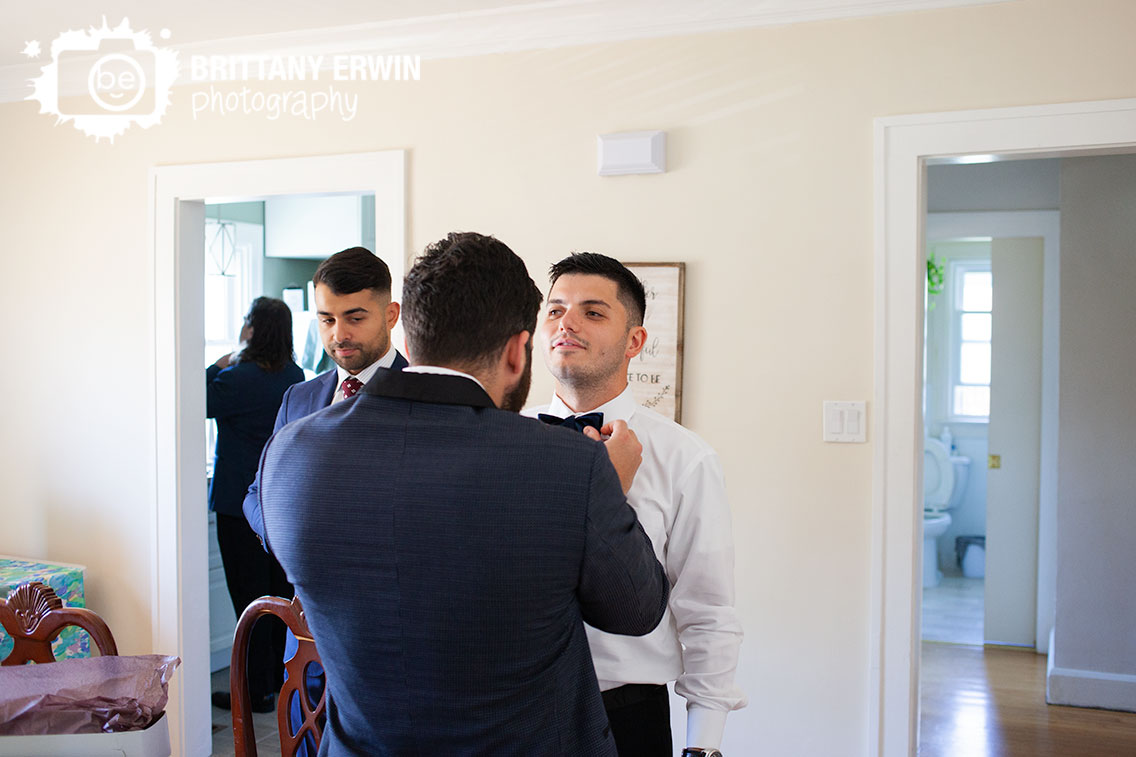 The-black-tux-rental-wedding-photographer-groom-getting-ready-bowtie-straightened-by-groomsman.jpg