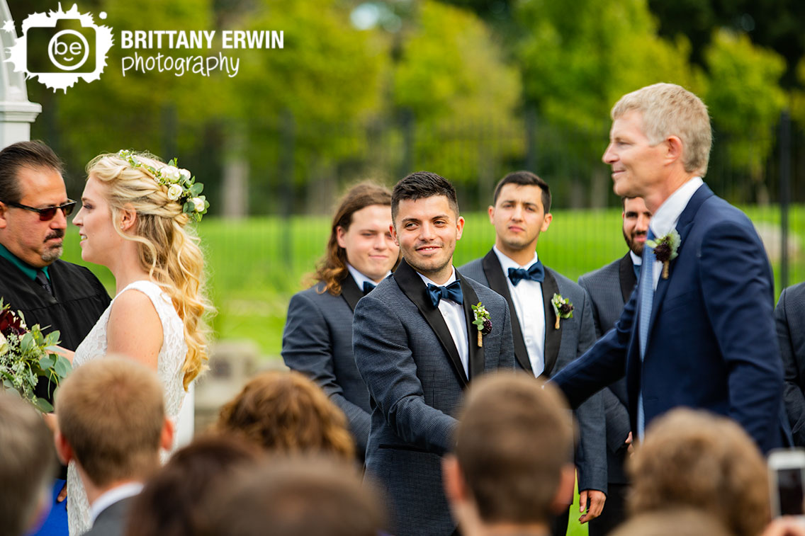 Garfield-Park-wedding-photographer-groom-watch-bride-shake-hands-with-father-of-bride.jpg