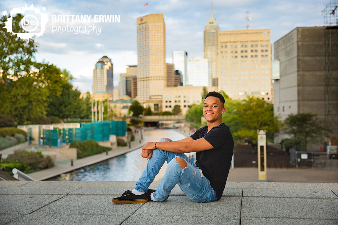 Downtown-Indianapolis-skyline-high-school-senior-portrait-photographer-sitting-at-top-of-stairs-canal-view.jpg