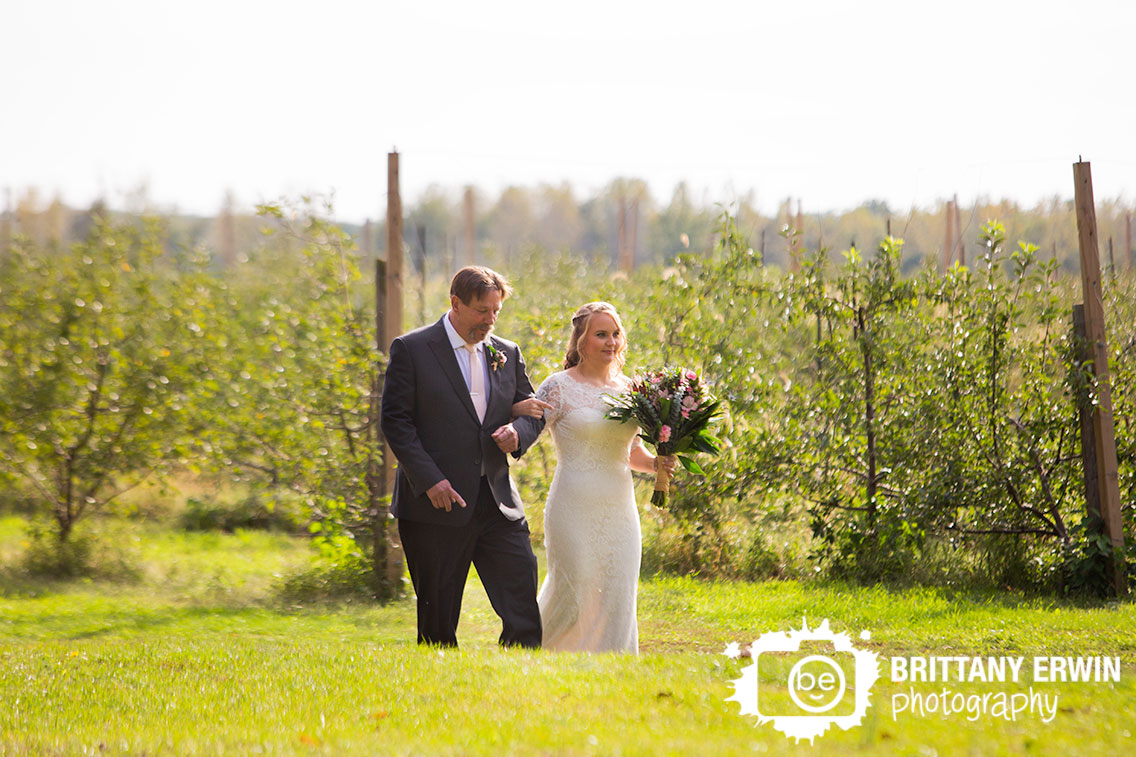 Wedding-photographer-bride-walking-down-aisle-with-father-orchard-apple-tree.jpg