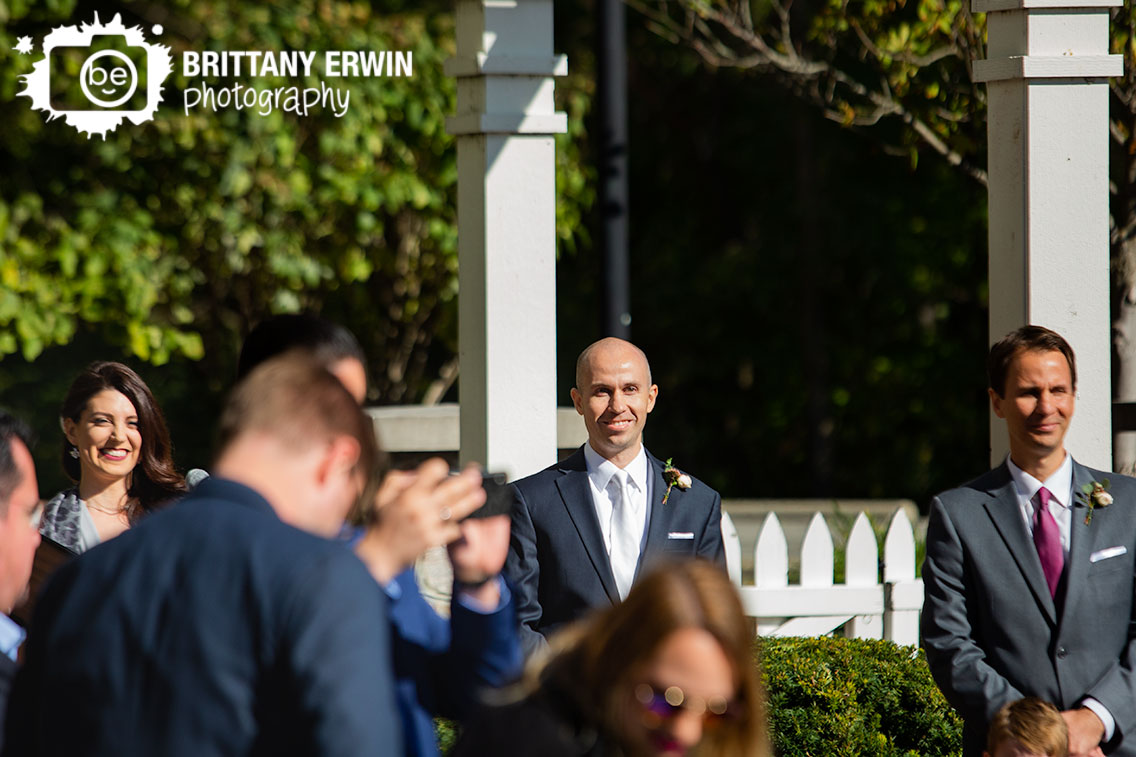 Groom-watching-bride-walk-down-aisle-at-pergola-Historic-Ambassador-House.jpg