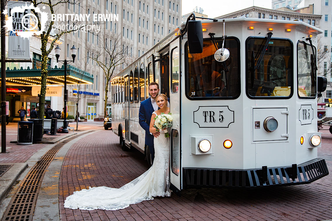 Downtown-Indianapolis-wedding-photographer-couple-on-trolley-long-train-on-monument-circle.jpg