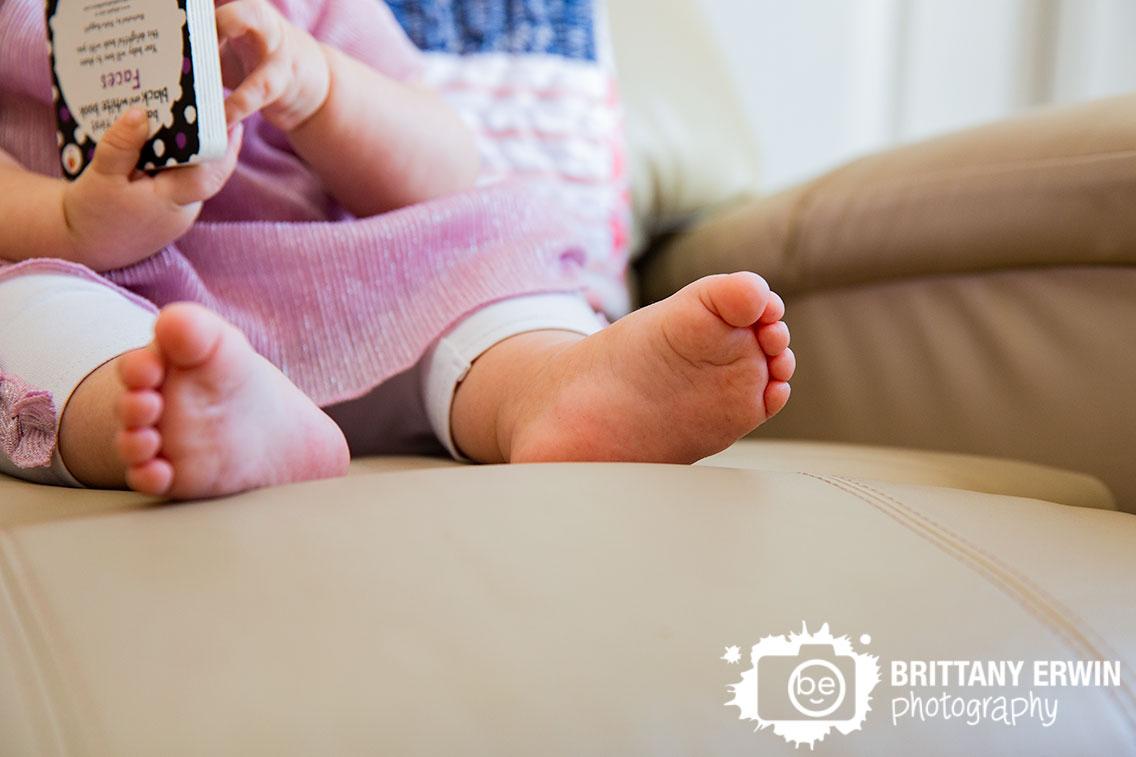 babygirl-sitting-in-chair-feet-while-reading-book-in-nursery.jpg