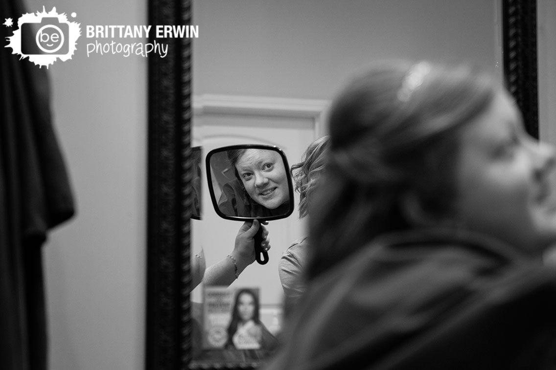 Indianapolis-wedding-photographer-bride-looking-at-hair-in-mirror-salon-and-spa-no-7.jpg