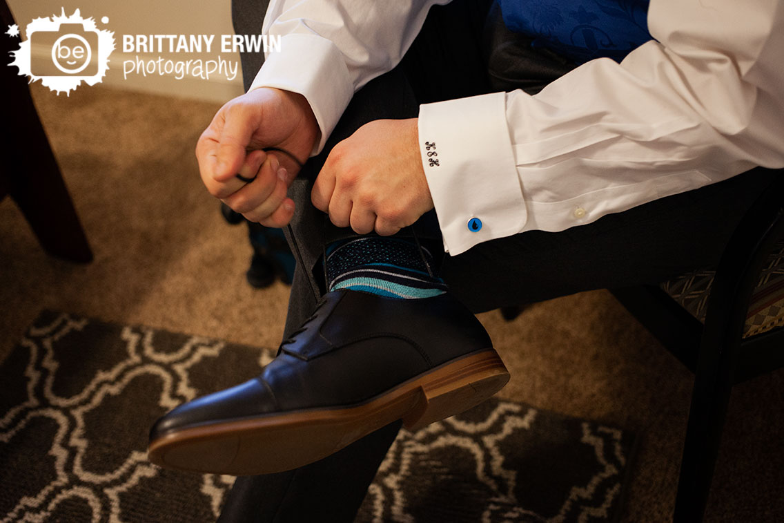 Indianapolis-wedding-photographer-groom-tying-shoes-water-cufflinks-blue-socks-initial-cuffs.jpg