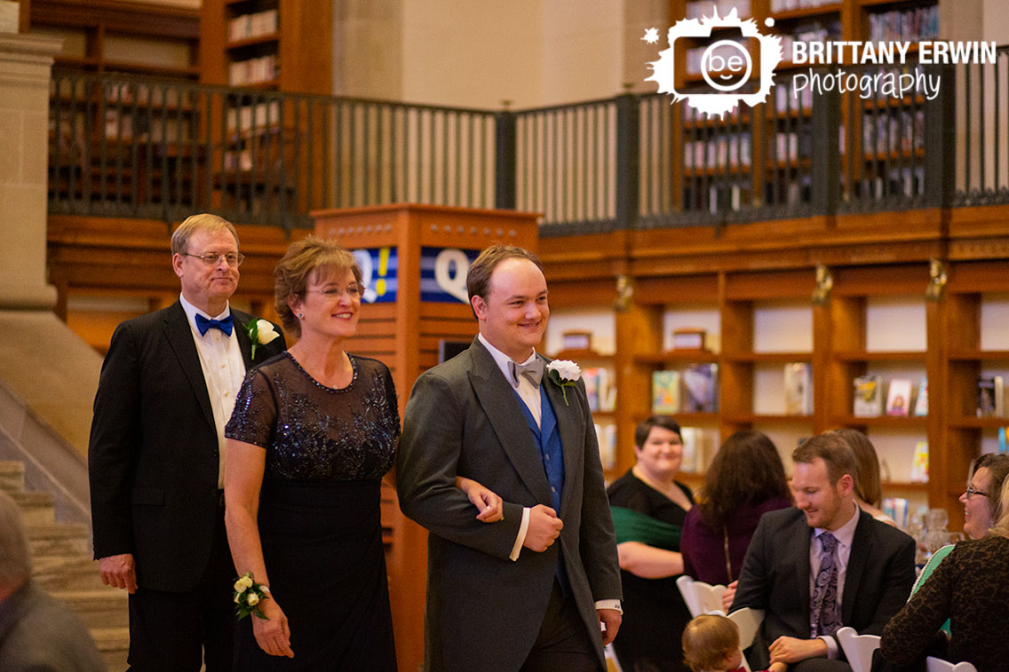Indianapolis-central-library-wedding-ceremony-photographer-groom-walking-down-aisle-with-mother-and-father.jpg
