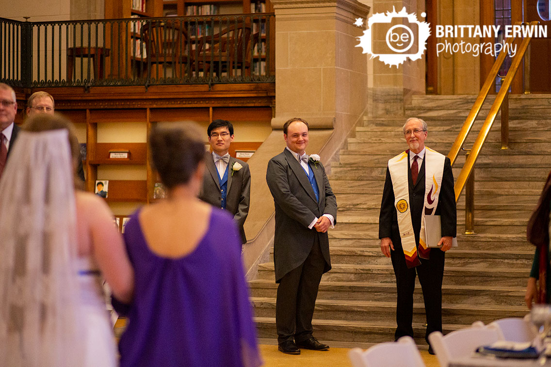 Indianapolis-central-library-wedding-ceremony-photographer-groom-reaction-bride-walking-down-aisle-with-mother-and-father.jpg