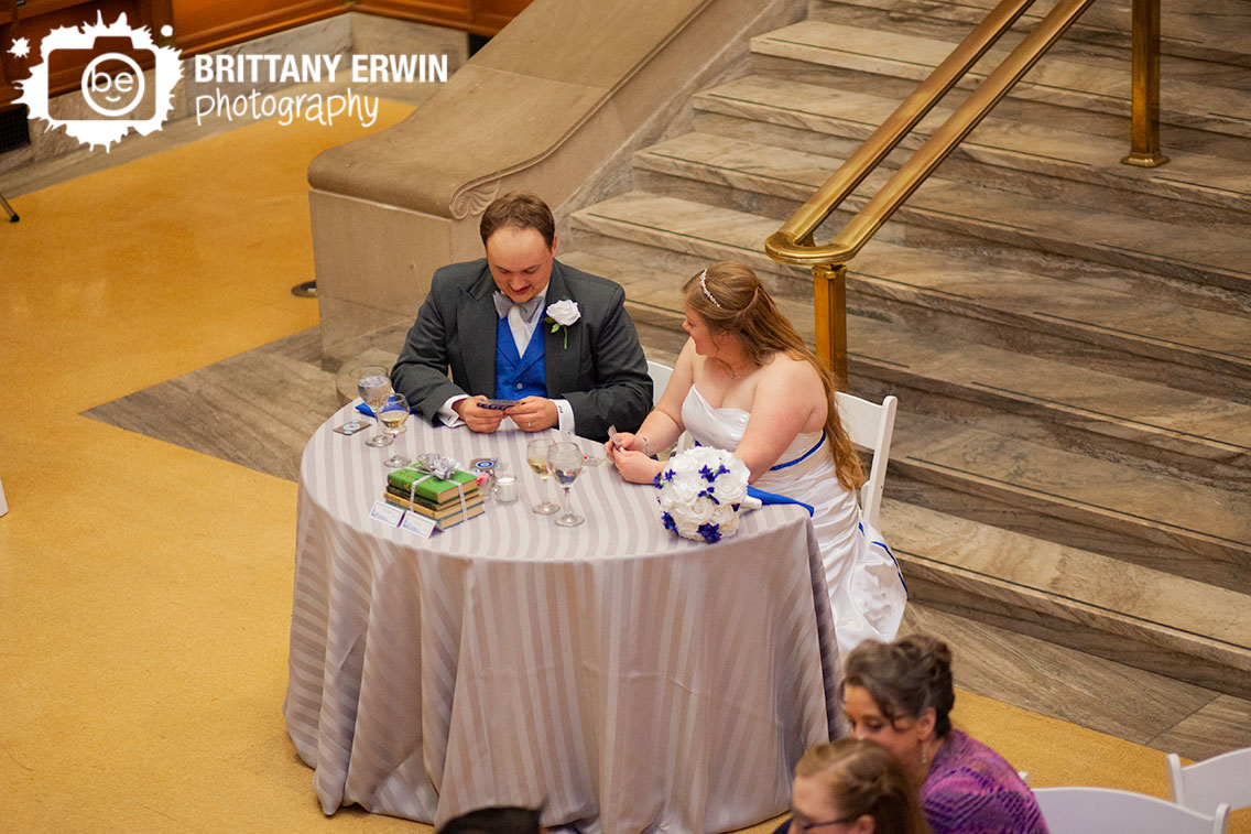 Indianapolis-central-library-wedding-photographer-first-game-couple-at-sweetheart-head-table-playing-cards.jpg