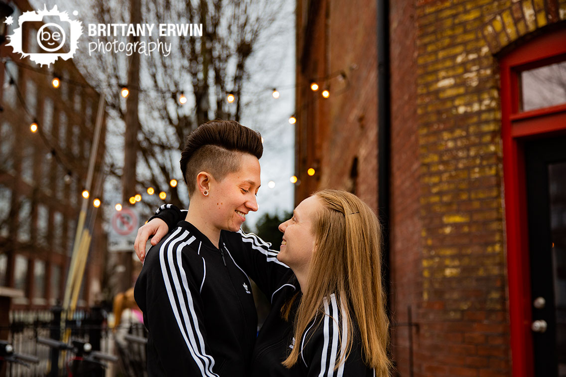 Indianapolis-engagement-portrait-photographer-Mass-Ave-couple-matching-track-suits-with-twinkle-lights.jpg