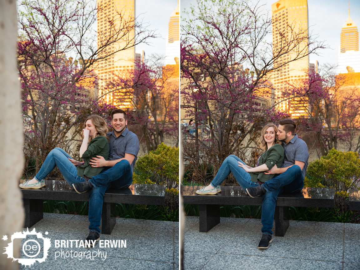 Indianapolis-skyline-portrait-engagement-photographer-couple-laugh-on-bench-spring-blooming-tree.jpg