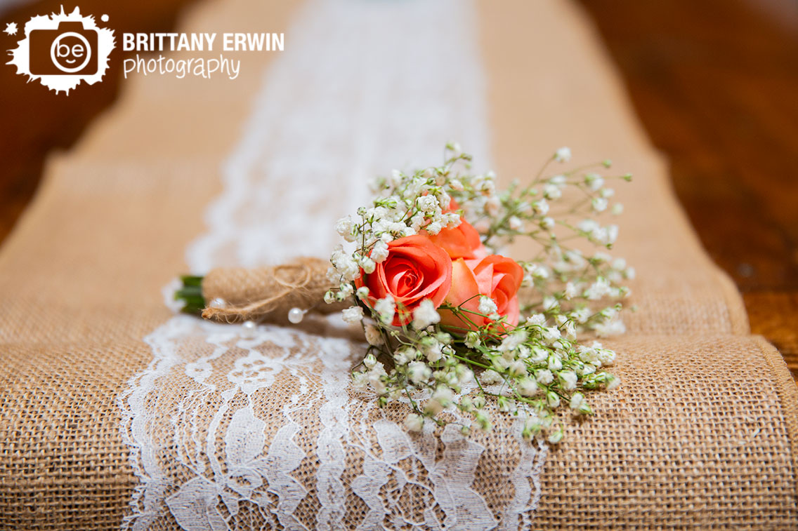 handmade-boutonniere-for-groom-made-with-pink-roses-and-babys-breath-resting-on-burlap-and-lace-table-runner.jpg