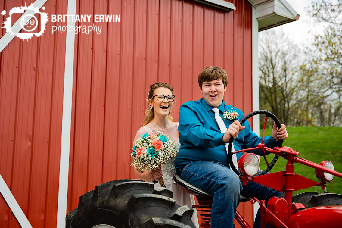 Indiana-bride-groom-on-red-tractor-outside-barn-laugh-silly-couple.jpg