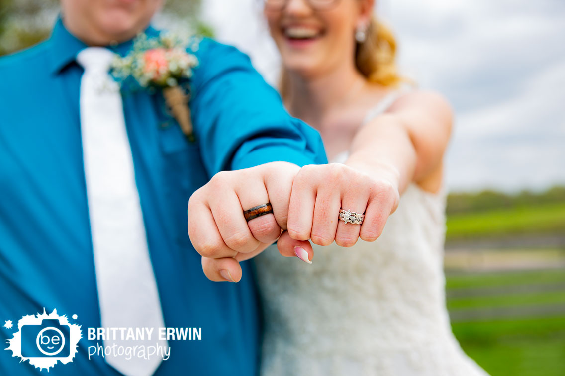 bride-and-groom-fist-hands-wearing-wedding-ring-bands-fun-laughing.jpg