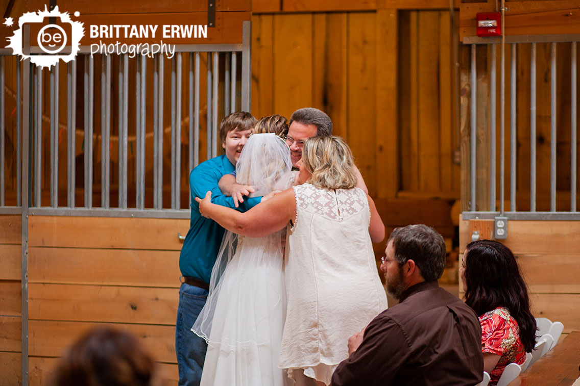 Indiana-wedding-photographer-bride-and-groom-group-hug-release-by-row-at-ceremony.jpg