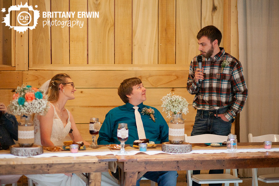 Rustic-Gatherings-LLC-wedding-barn-venue-couple-at-head-table-toast-by-best-man.jpg
