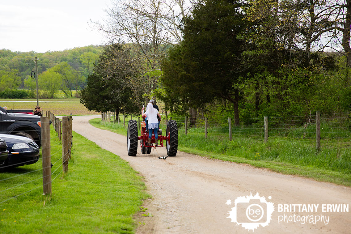 Bride-and-groom-exit-on-red-antique-tractor-can-string.jpg