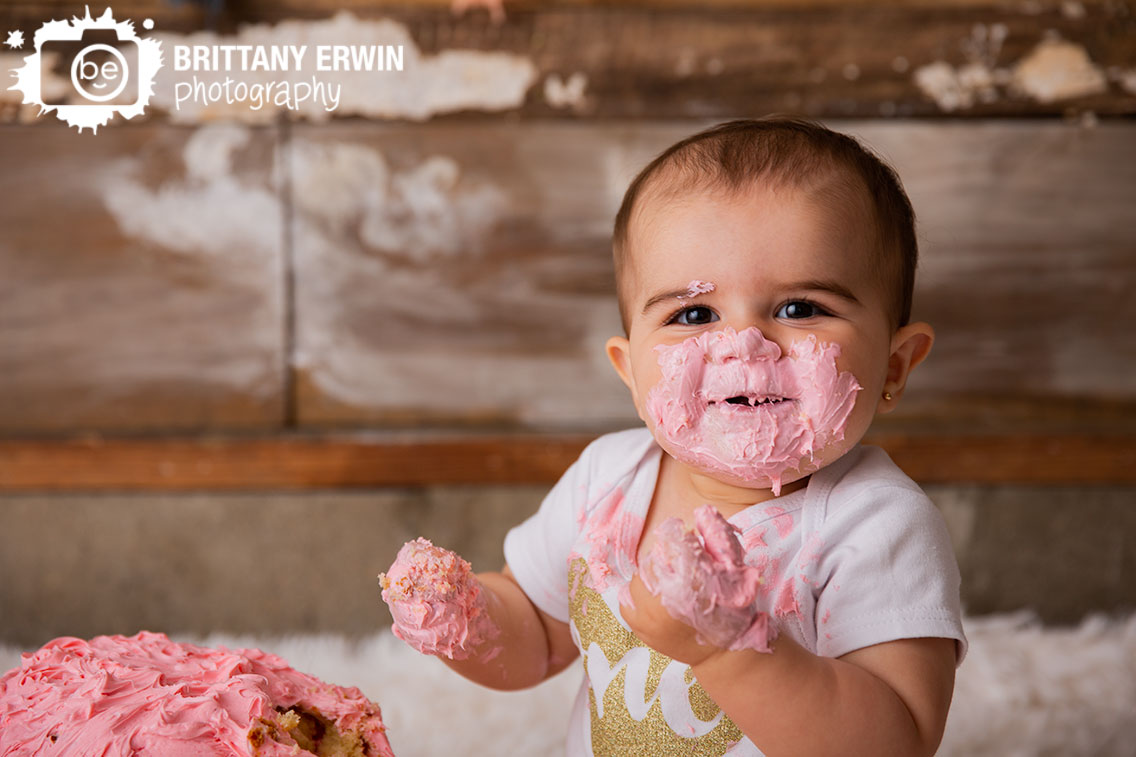 Cake-smash-studio-portrait-photographer-one-sparkle-onesie-pink-rosette-iciing.jpg