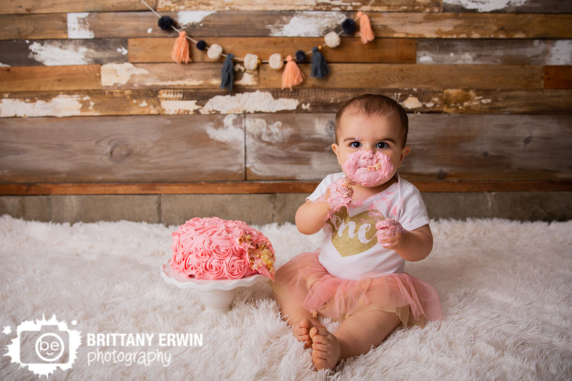 Indianapolis-portrait-studio-photographer-cake-smash-home-made-rosette-pink-icing-baby-girl.jpg