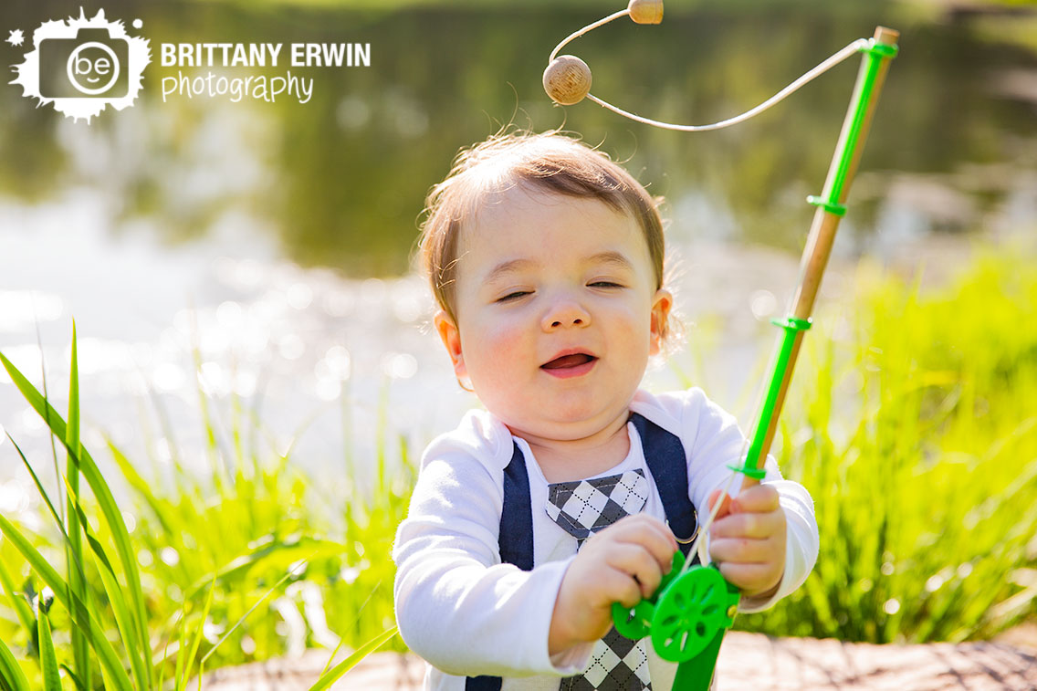 spring-portrait-photographer-first-birthday-boy-fishing-pole-by-pond.jpg