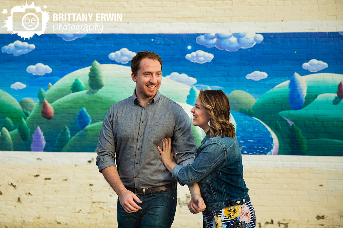 Indiana-engagement-portrait-photographer-couple-walking-by-wall-mural-trees-rolling-hills-with-clouds.jpg
