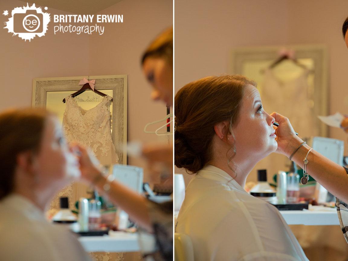 dress-hanging-from-mirror-behind-bride-having-makeup-done.jpg