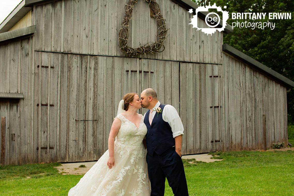 Hidden-Brook-Acres-barn-wreath-over-doors-couple-kiss.jpg