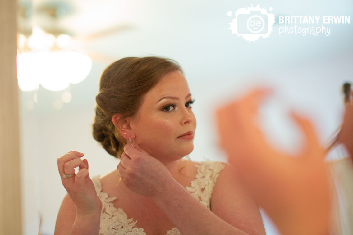 Indiana-wedding-photographer-bride-getting-ready-put-on-earrings-in-mirror.jpg