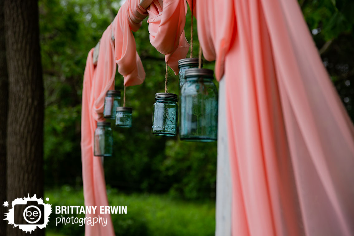 mason-jar-hanging-from-arbor-wedding-altar-space-pink-drapery.jpg