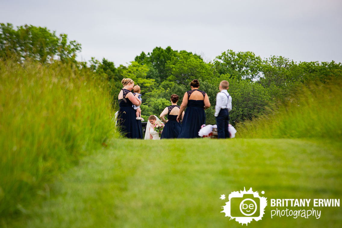 bride-walking-up-to-ceremony-space-bridesmaids-waiting.jpg