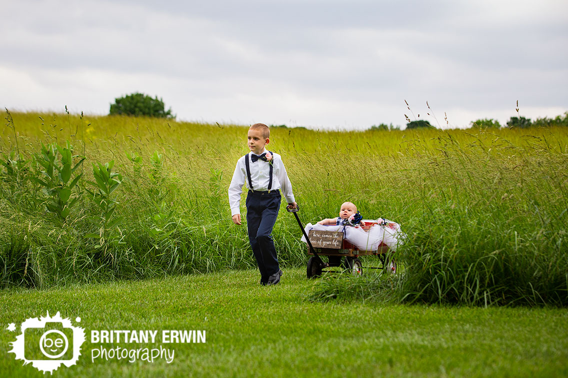 ring-bearer-pulling-wagon-with-baby-flower-girl-outdoor-summer-wedding.jpg