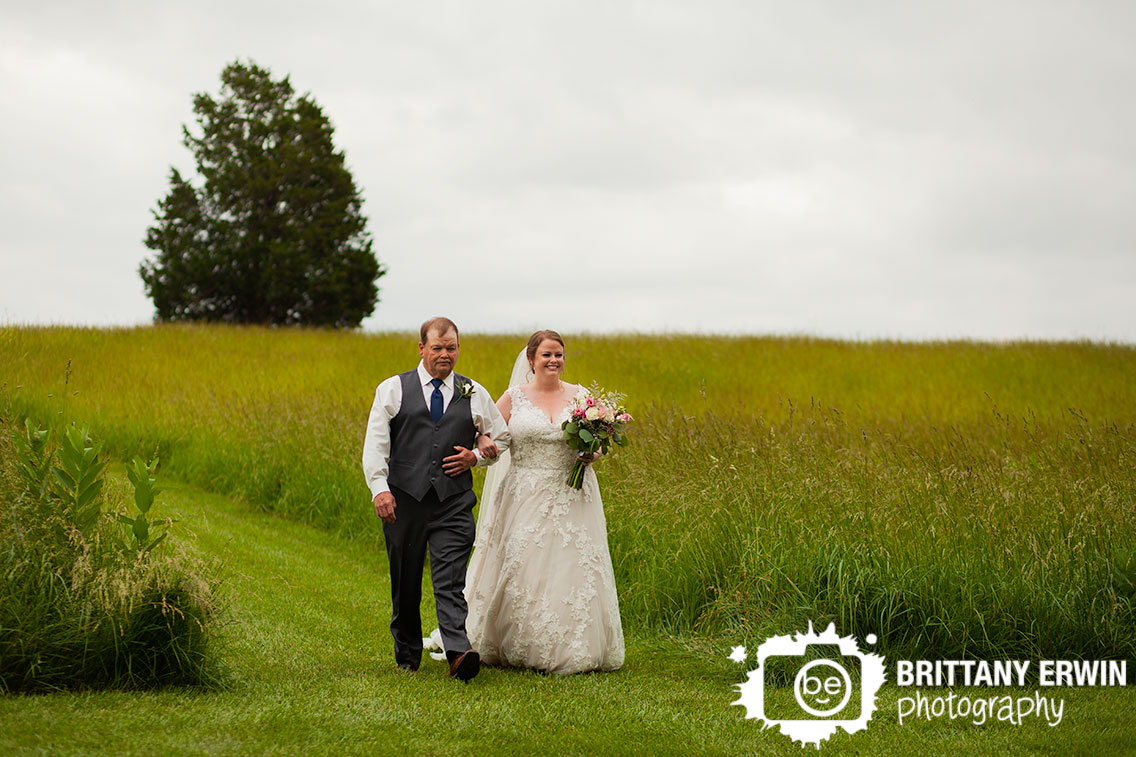 bride-walking-down-aisle-with-father-tall-grass-outdoor-ceremony.jpg