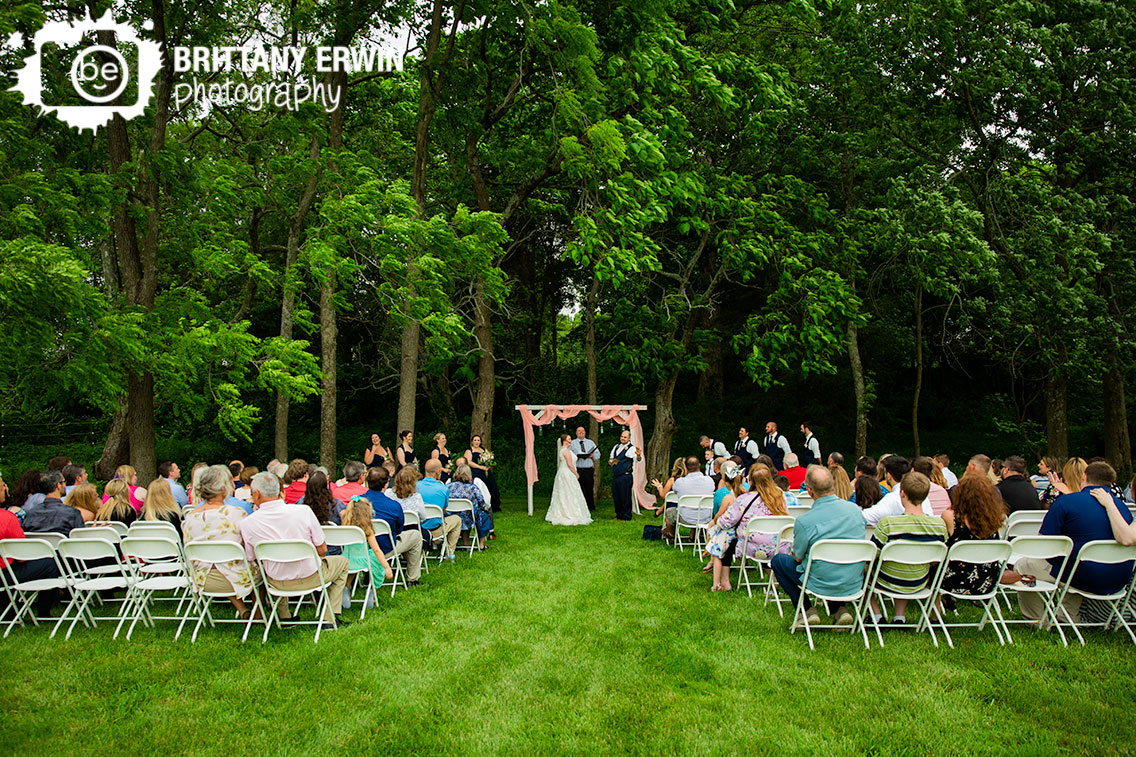 outdoor-wedding-ceremony-couple-vows-groom-funny-laughing-bridal-party.jpg