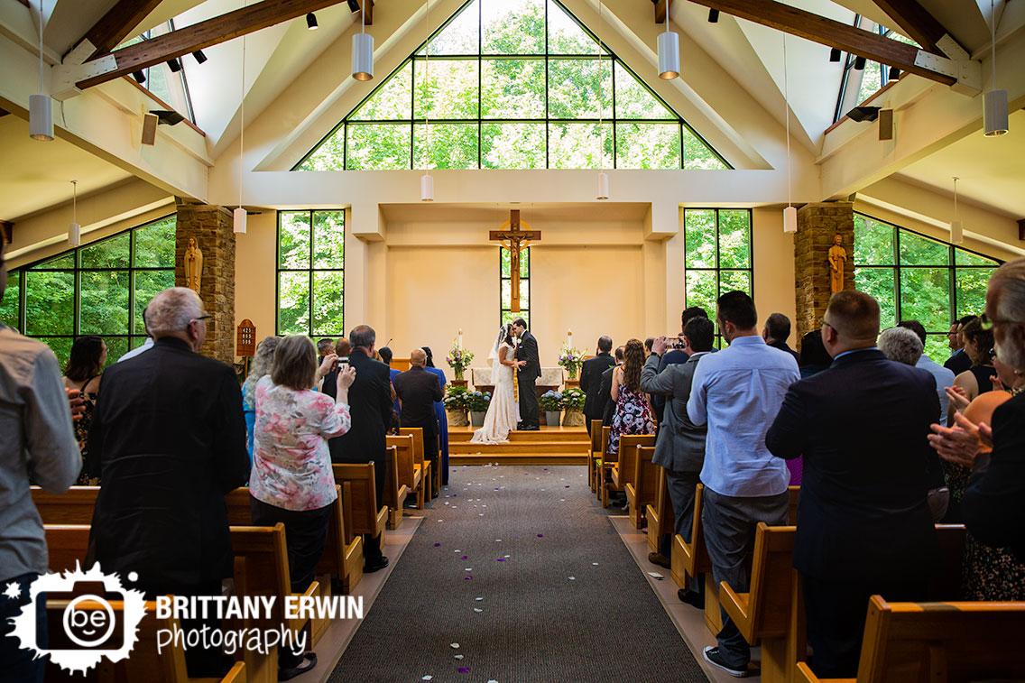 first-kiss-catholic-wedding-ceremony-couple-at-altar.jpg