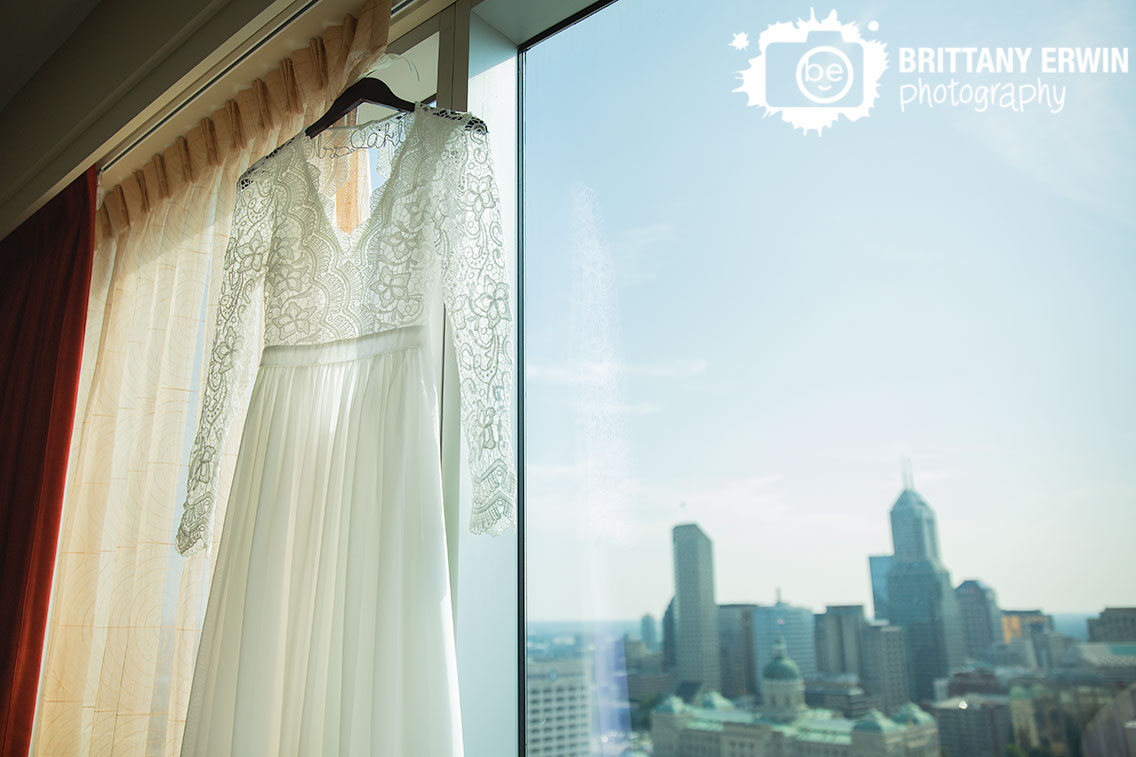 custom-hanger-bridal-gown-dress-lace-sleeves-hanging-in-window-JW-Marriott-skyline-Indianapolis.jpg