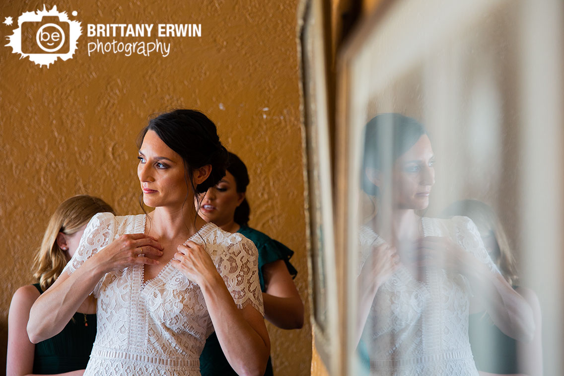 Bride-putting-on-dress-reflection-in-picture.jpg