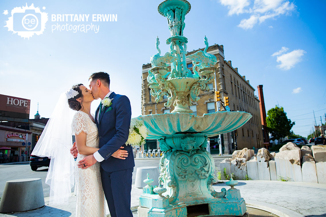Fountain-Square-Indiana-wedding-photographer-couple-at-the-fountain-kiss-with-city.jpg