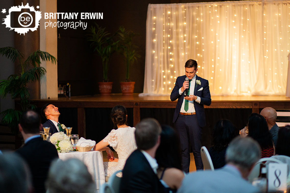 Best-man-giving-toast-at-wedding-reception-groom-laugh-reaction.jpg