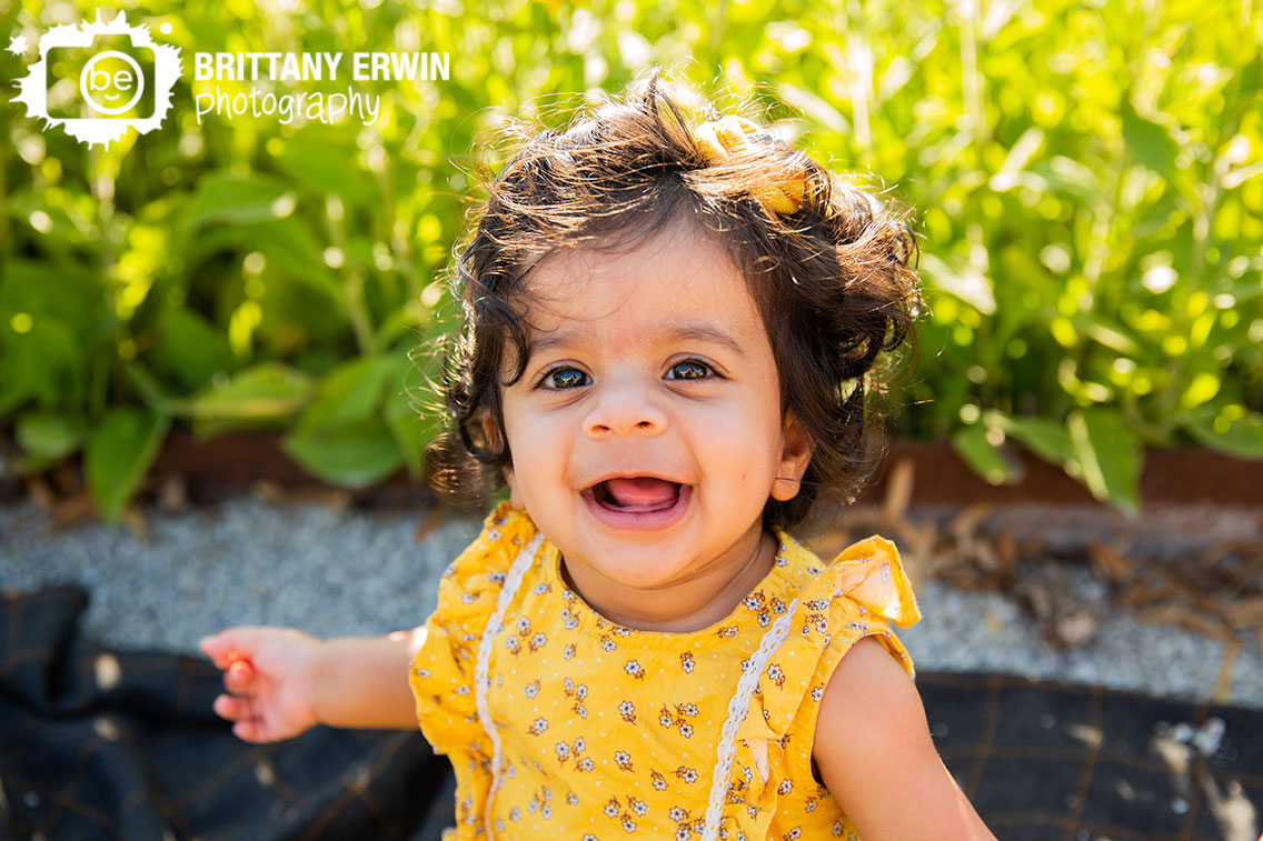 milestone-portrait-photographer-summer-flower-lined-path-baby-girl-yellow-romper.jpg