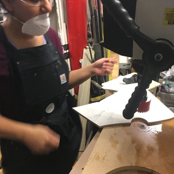 Here she has attached a hole saw for porcelain cutting to the VFL's drill press to cut a series of holes in the tile, but unfortunately the tile cracked!