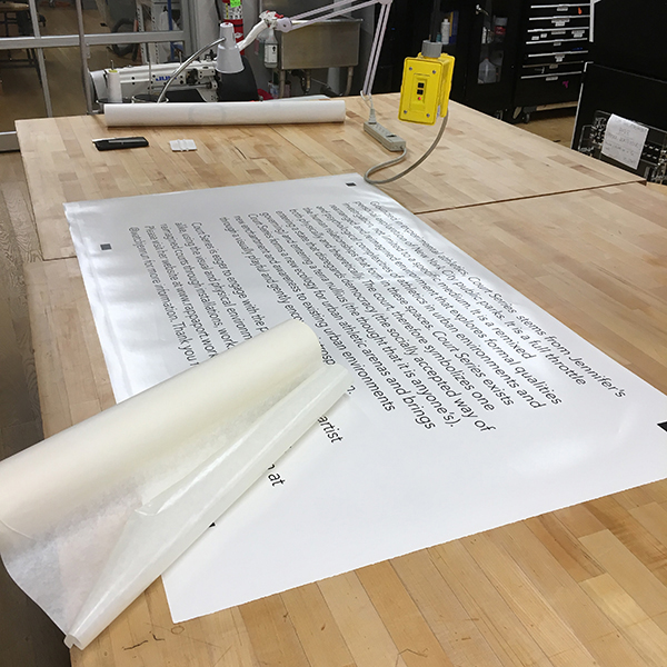 First-year  MFA Fine Arts  student Jennifer Rappaport is preparing vinyl text for the presentation of her work at Open Studios.