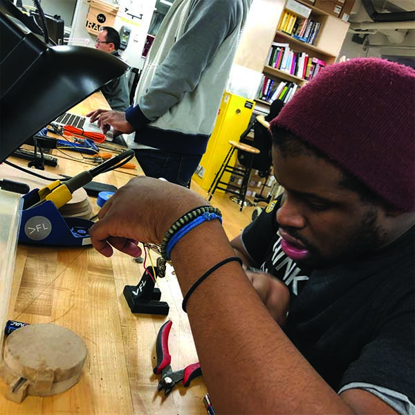 MFA Interaction Design  1st year Student Kenrick Ramsay is working diligently on his final Physical Computing project. He is seen here soldering LED strips and wire that will become an online bus ticketing system for the SVA Shuttle.