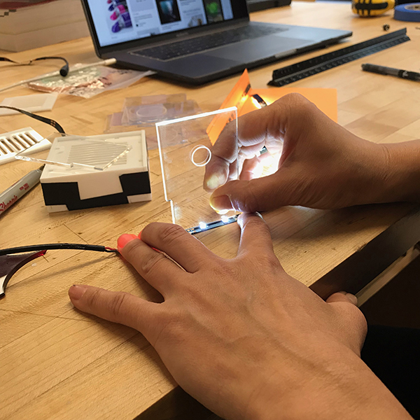 Her process starts off by cutting acrylic sheets and assembling them to make customized light-boxes.