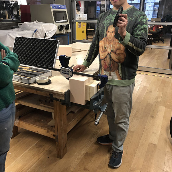 Chester is explaining the basics of the lathe set up and operation as it is the first time for both students. They're working on their prototypes for their  MoMA design store  pitches.