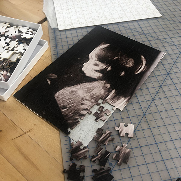 She's printing various sentimental photos of family members and cutting them into puzzle
